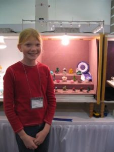 Lauren Megaw as a child posing in front of her award-winning Tucson Show mineral display