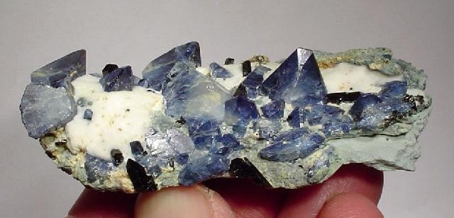 A striking rich benitoite plate dominated gemmy 1 2 cm upright crystal