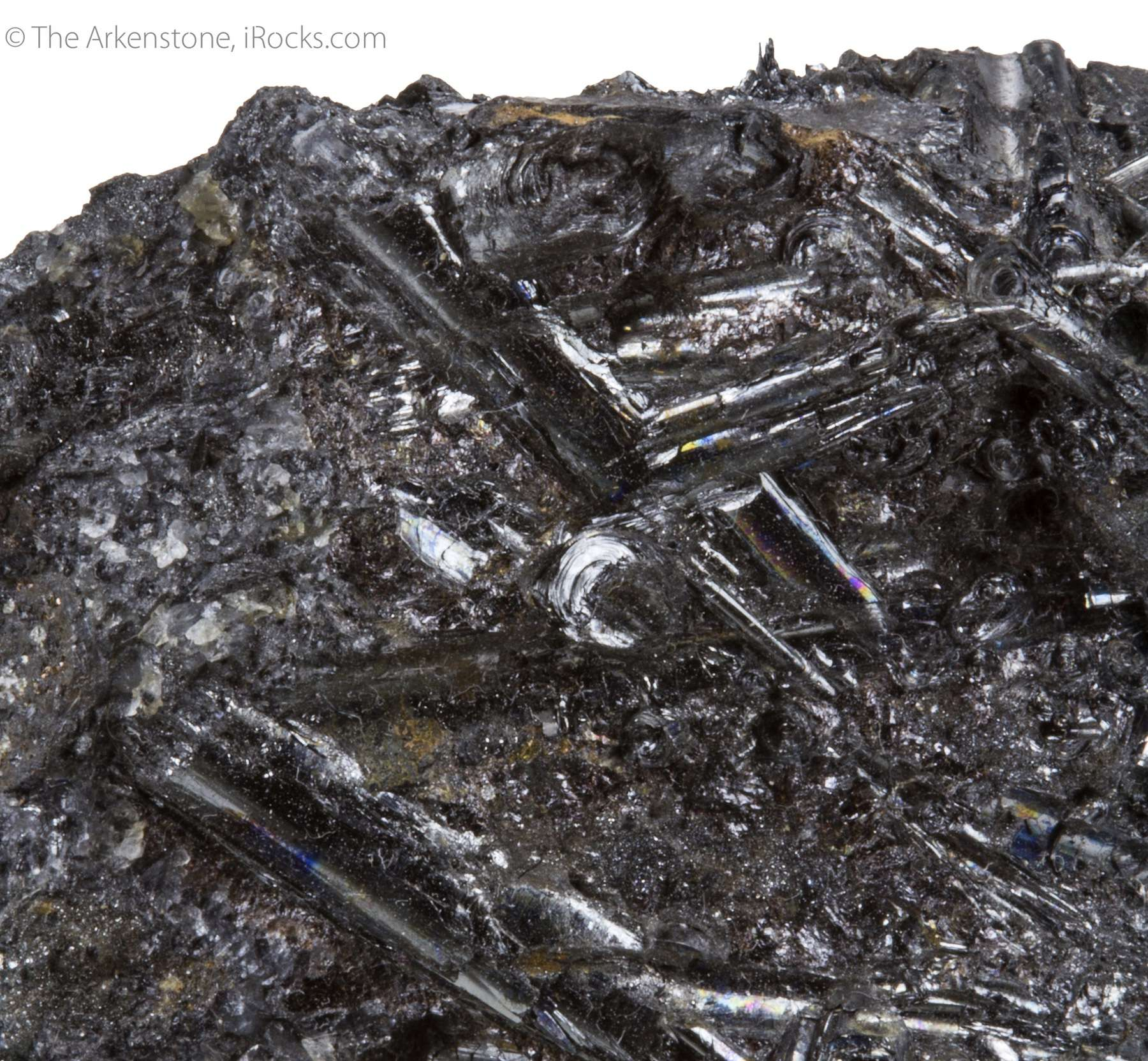 Partially embedded massive ore slender prisms 2 cm length splendent