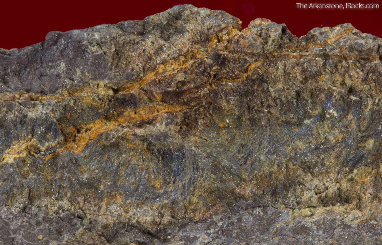 Dark gray metallic divergent lamellar aggregates suredaite occupying 3